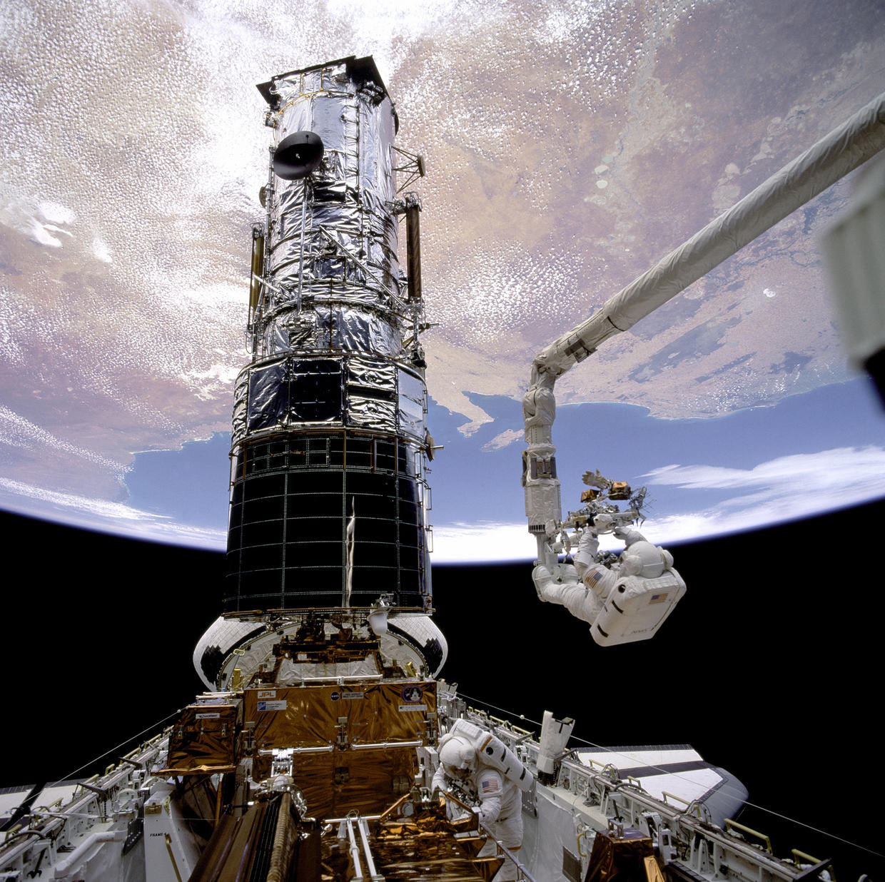 Endeavour astronauts repairing the Hubble Space Telescope in space