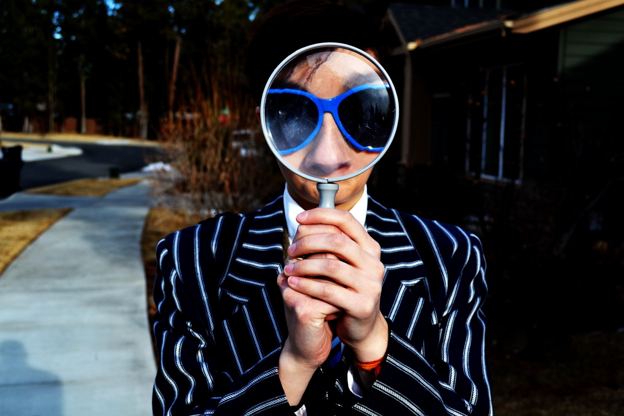 A person holds up a magnifying glass in front of their face.