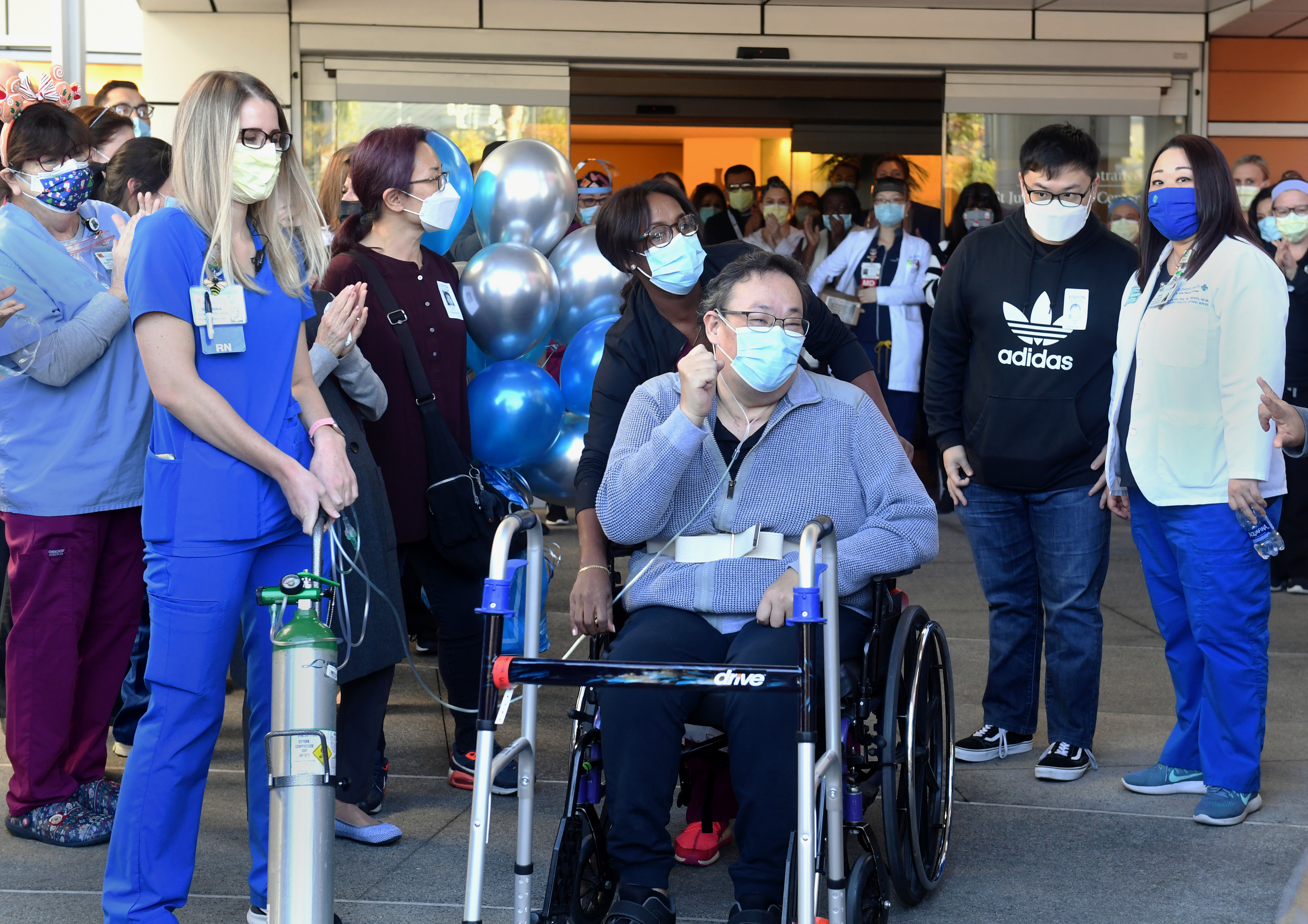 Hospital staff applaud Southern California resident Daniel Kim as he heads home after a five-month battle with COVID-19