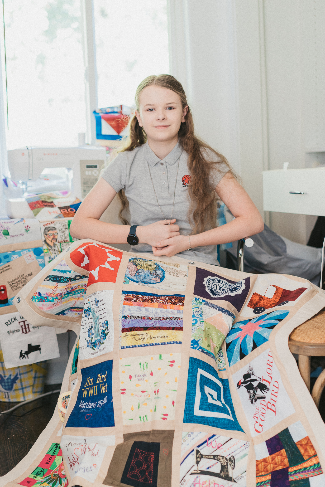 Eighth grader Madeleine Fugate sits in a chair with a panel from the COVID-19 memorial quilt draped over her lap