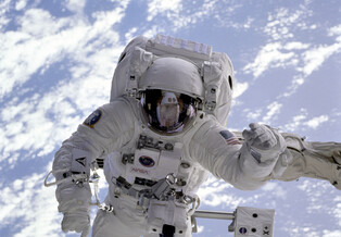 An astronaut conducts a spacewalk with Earth visible behind him.