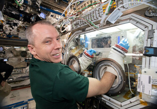 Mission Specialist Drew Feustel performs an experiment on the International Space Station.