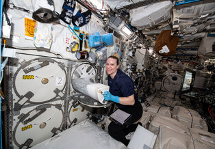 Astronaut Kate Rubins loads tissue samples into a freezer on the International Space Station.