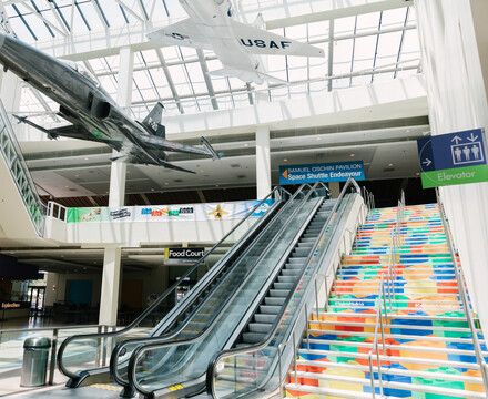 Escalators and stairs leading from Edgerton Court to Disney Science Court. Stairs feature LEGO brick art print on side panels and aircraft are seen displayed overhead