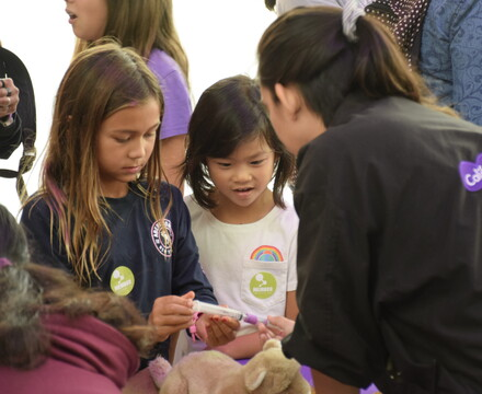Two young girls enjoy a science activity with a Science Center staff member