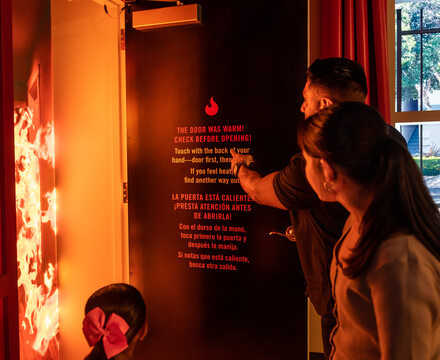 Latino family opening door in Fire! Science & Safety Exhibit