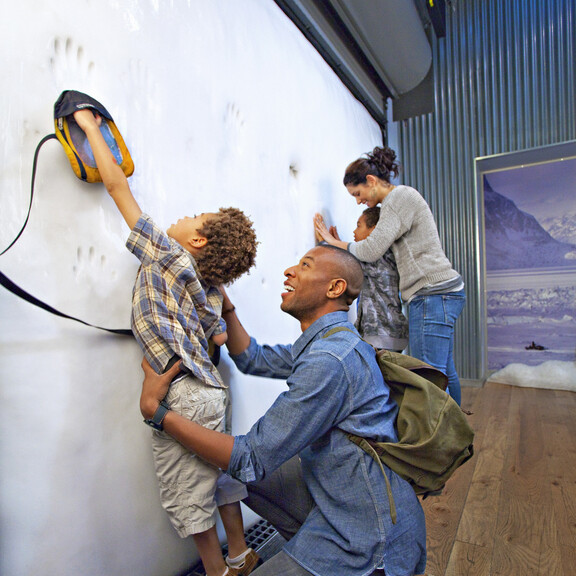 Family touching ice wall inside Ecosystems Poles gallery