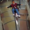 A boy balances a bike on a wire, three stories above the floor below.