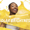"Image of yellow paint splashed around an African American woman with the words ""solar brightness"" on the photo"