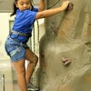 Young girl wearing harness climbs artificial rock wall