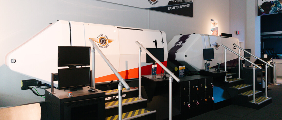 PulseWorks Flight Club Simulators in Creative World exhibit gallery - Two white rectangular simulators with triangular noses. Small set of stairs leads to each simulator's entry point