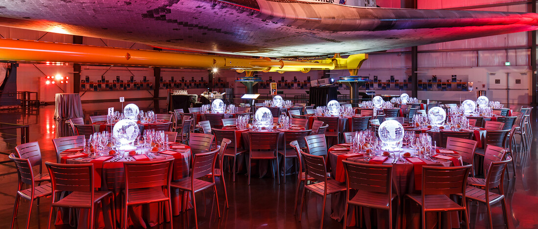 Seated Dinner under the Samuel Oschin Pavilion lit deep red with glowing globe centerpieces