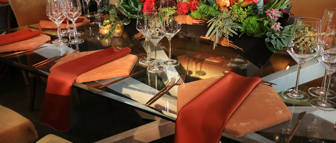 Discovery Ball tabletop with Saltillo tole chargers, burnt orange napkins, glassware, and floral centerpiece