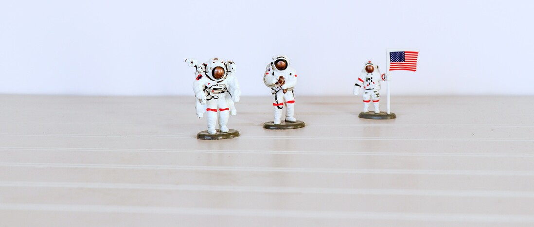 Three US astronaut plastic toys on light tabletop