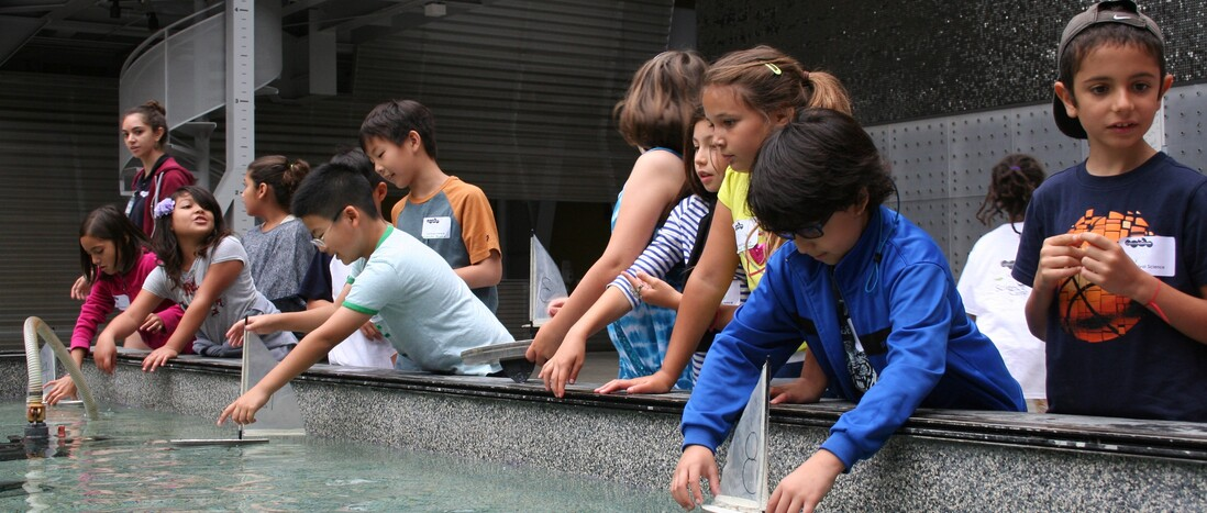 Youth participating in a field trip program, testing boats in the Water Works pool