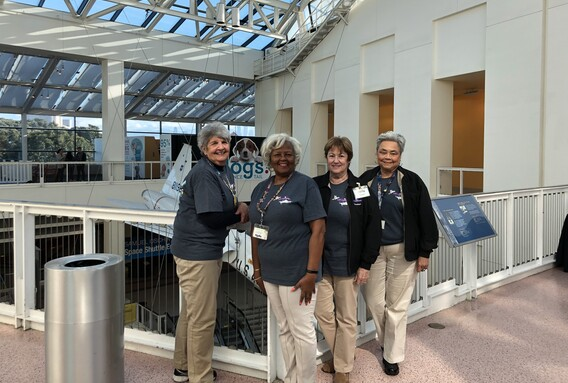 Four event volunteers wearing Science Center t-shirts featuring the new exhibition and khaki pants uniforms pose on the third floor of the Science Center