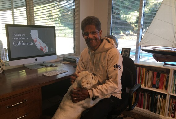 Curator of Aerospace and contact tracing team leader Ken Phillips sits at at a desk in his home office and pets his bulldog